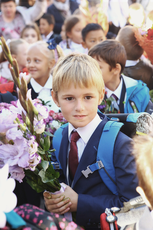 solemn: Moscow, Russia - September 1, 2016: Unidentified girls with flowers bouquet on solemn meeting of first grade kids, called the Day of Knowledge, signify the beginning of school year. Editorial