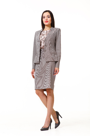 straight jacket: indian business executive woman with straight hair style in office gray skirt suit jacket high heel sandals shoes going full body length isolated on white Stock Photo