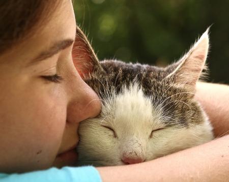 De tienermeisje knuffel kat close-up portret op de zomer tuin achtergrond