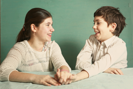 sibling rivalry: teen siblings boy and girl srtugglig arm wrestling close up photo