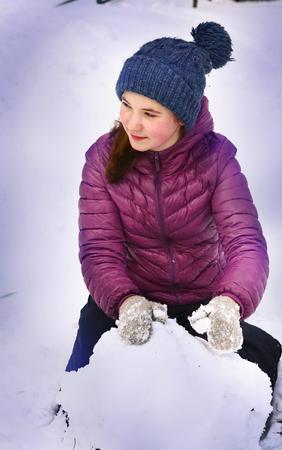 Teen hübsches Mädchen rollen Schneeball Winter Porträt Nahaufnahme