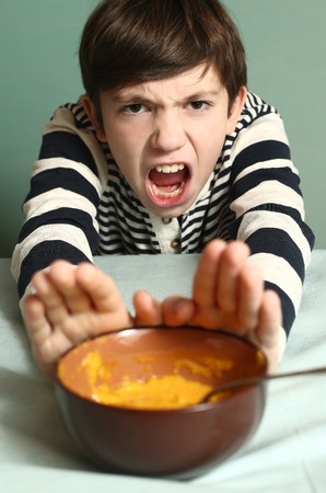 preteen handsome boy refuse from eating smashed pumpkin soup