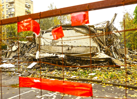dismantle: destroyed old house behind the fence with warning red tape emogy