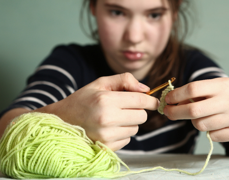 teen pretty girl knitting by hook with pistashio yarn ball close up photo