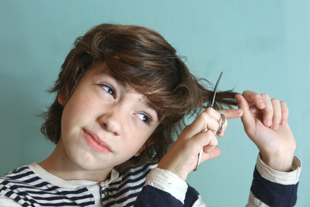 his: preteen handsome boy with scissors try to cut his hair by himself close up photo