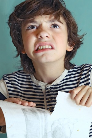 rage: preteen handsome boy in rage about his drawing close up photo Stock Photo