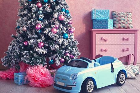 habitación de color rosa con la decoración de año nuevo de Navidad con cuadro presente y el árbol de coches Foto de archivo