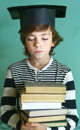 Prodigy: preteen handsome boy in graduation cap with book pile close up photo