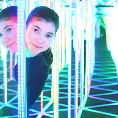 concave: Teenage pretty girl in mirror maze try to find way out Stock Photo