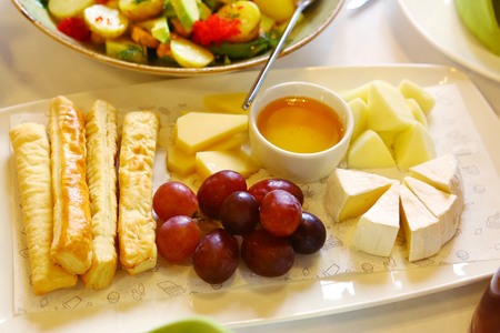 cheese plate with honey saucer grapes and bread stick close up photo Stock Photo