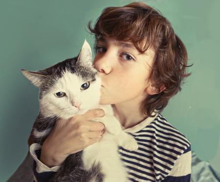 Preteen gato chico guapo con el gato tom Besos cerca encima de la foto Foto de archivo - 65776017