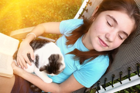 teenager girl sleeping in chaise lounge with cat and book close up portrait