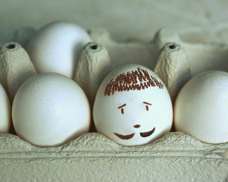 crater: eggs white with drawn mans face close up photo. Raw eggs, crater egg Stock Photo