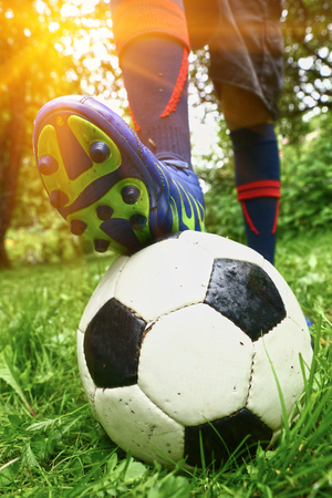 foot with footbal boots on the ball close up photo. Boot on ball. Stock Photo
