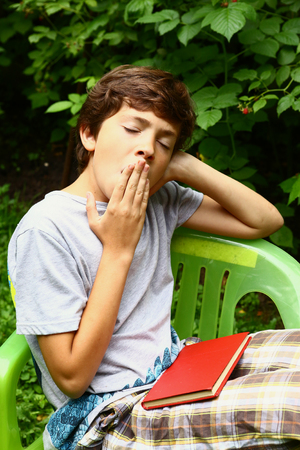 the yawn: boy with book yawning close up photo in the summer garden. Boy yawn. Stock Photo