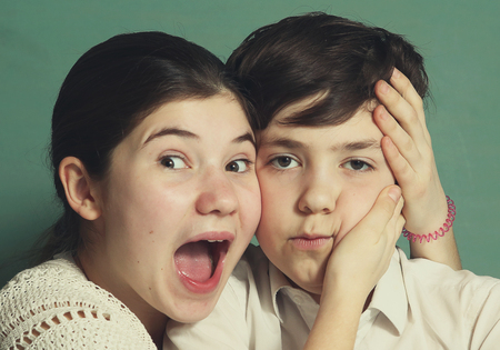 brother sister fight: teen siblings brother and sister grimacing close up portrait. Boy girl siblings grimace.