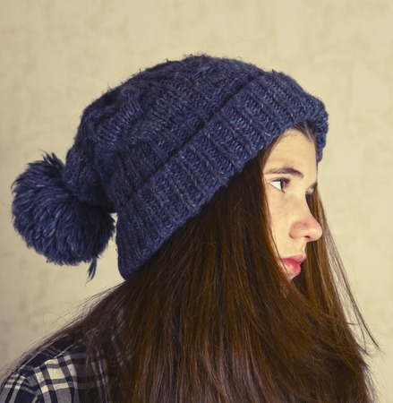 pompom: teenage girl in knitted blue hat with pompom close up portrait. Teen girl in winter hat.