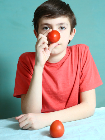 preteen handsome boy with tomato nose close up photo