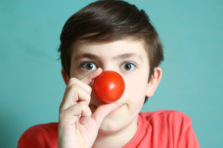 nose close up: preteen handsome boy with tomato nose close up photo