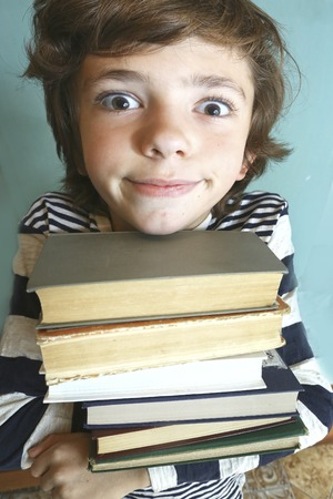 prodigy: preteen handsome boy with book pile close up photo