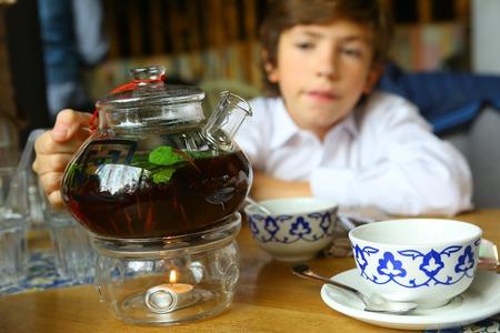 adn: niño preadolescente con el ganado de té caliente en mantener la vela ardiente del ADN de las tazas de té cerca retrato Foto de archivo