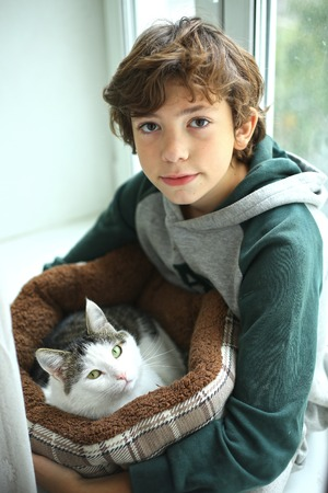 devotional: preteen handsome boy with cat in cat bed close up photo