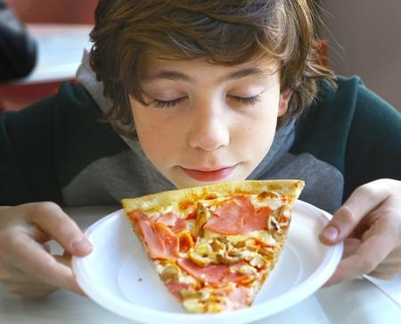 Pequeño niño preadolescente que huele pizza cerca photo Foto de archivo - 65776220