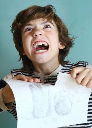 preteen school boy in rage tear ripping up his work