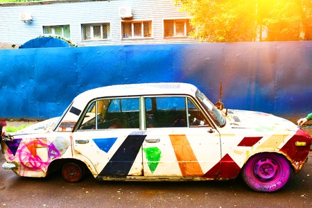 old broken car painted multicolord close up photo