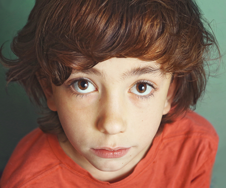 reproach: preteen handsome boy expressive close up serious portrait with big eyes