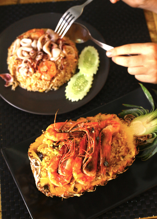 cuke: Freshly prepared pineapple fried rice with seafood - prawn, squid, octopus served inside of a pineapple carved like a bowl. Stock Photo