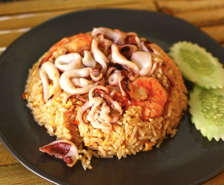 octopus with prawn and rice thai dish close up photo with spoon and fork Stock Photo