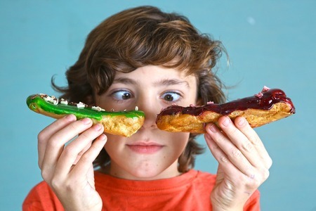 preteen handsome boy with eclair french dessert in hands cant choose the one Stock Photo