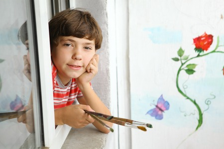 preteen handsome artist boy with brushes and his painting on the background wall