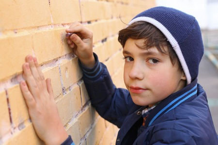 educative: preteen handsome boy in blue hat drawing on the wall close up portrait
