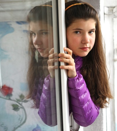 thick hair: preteen euripean girl with long brown thick hair close up photo look out from the window with reflection