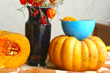phisalis: autumn cut pumpkin still life with phisalis and viburnum in blue jar and bowl with smashed pumpkin on the table close up photo