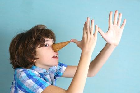 preteen knappe jongen grimassen met ijs kegel Pinocchio uitvoeren van close-up grappige foto Stockfoto