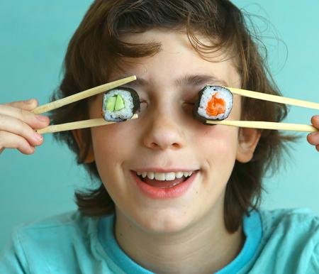 Apuesto muchacho preadolescente con el rollo de sushi establecido y se adhieren hambre Foto de archivo - 65777934