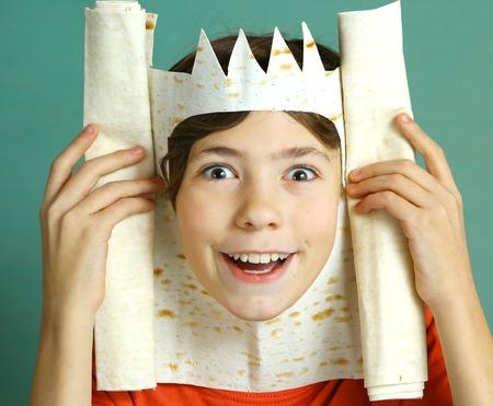 pantomima: apuesto muchacho preadolescente con una rica imaginación representan rey con pan de pita corona feliz sonriente foto de cerca sobre fondo azul Foto de archivo