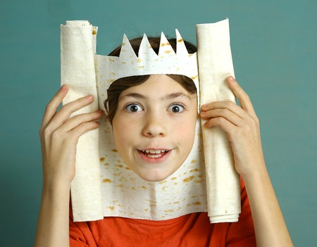 sombre: preteen handsome boy with rich imagination represent king with pita bread crown happy smiling close up photo on blue background