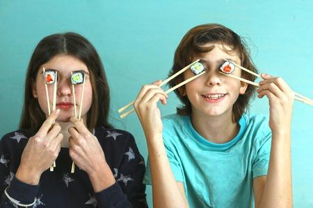 teen broers en zussen jongen en meisje kinderen met sushi avocado en zalm close up smiling photo