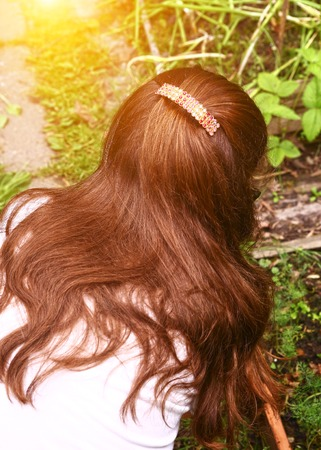 hairclip: long thick dark hair with hairclip close up photo from back on outdoor summer background Stock Photo