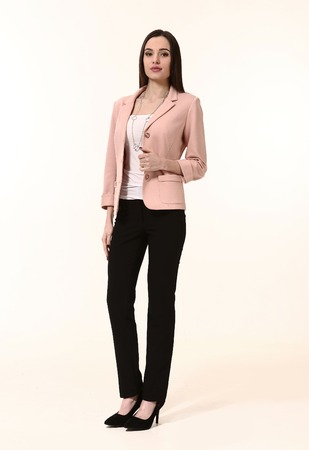 straight jacket: woman straight hair style in two pieces pink jacket trousers power pant suit high heels shoes full length body portrait standing isolated on white