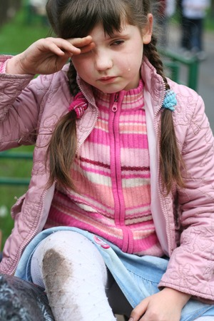 long faced: little girl with plaits fall down hurt her leg crying Stock Photo