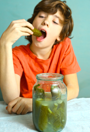 preteen boy eat marinated salted cucumber from jar close up portrait Stock Photo