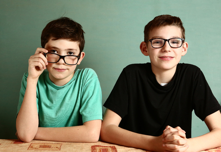 two teenager boys in myopia glasses close up portrait on blue wall background Stock Photo