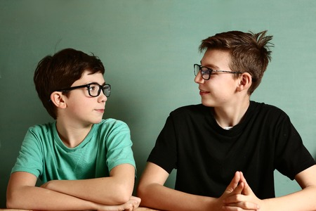 sense of sight: two teenager boys in myopia glasses close up portrait on blue wall background Stock Photo