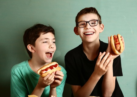 two preteen boys with hot dog close up photo in fast food chain restaurant