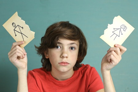 wait: sad preteen boy unhappy about parents divorce, hold man and woman paper drawing torn apart